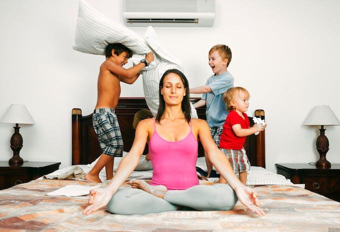 femme devant trois enfants qui jouent sur un lit