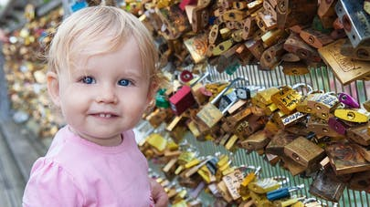 Une petite fille blonde sur le pont des arts, à Paris