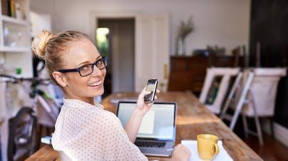femme  souriante devant son ordi chez elle