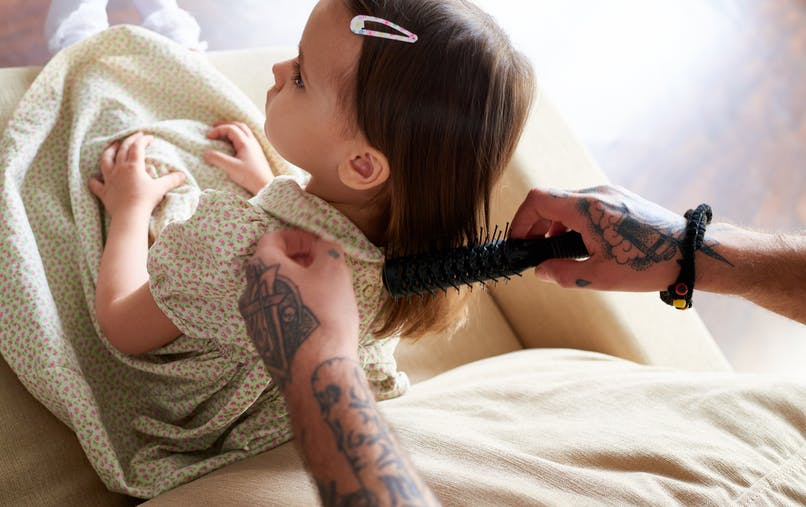 papa démêle cheveux petite fille