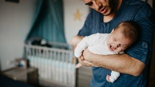 bébé qui pleure dans les bras de sa mère