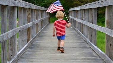 un petit garçon marche avec un drapeau américain à la main