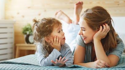Une maman et sa fille parlent allongées sur un lit