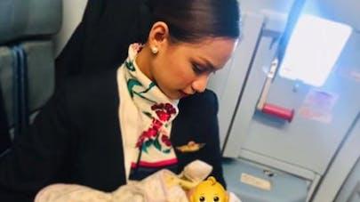 une hotesse de l'air allaite le bébé d'une passagère