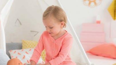 petite fille qui joue à la poupée