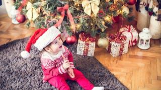 enfant au pied du sapin de Noël