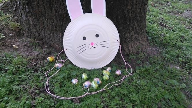 Un panier à œufs de Pâques avec des assiettes en carton
