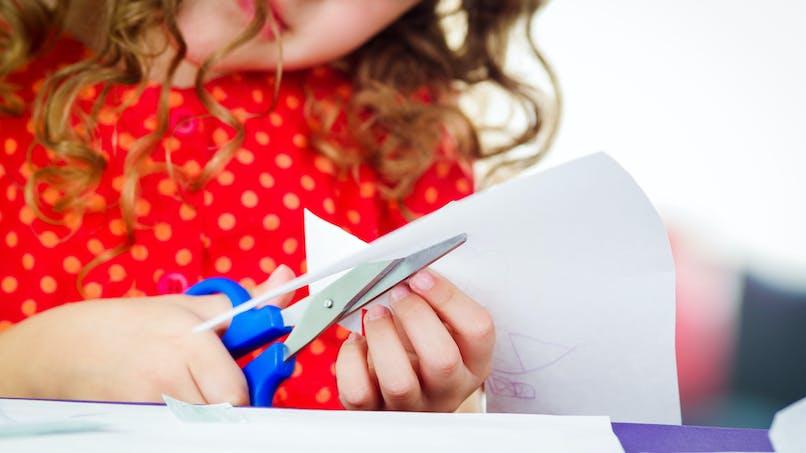 petite fille qui découpe du papier