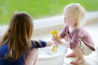 petite fille qui fait la lessive avec sa mère