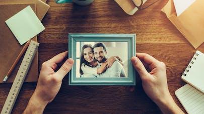 Gros plan de mains de femme qui tient une photo de couple. Préparation du dossier d'agrément.