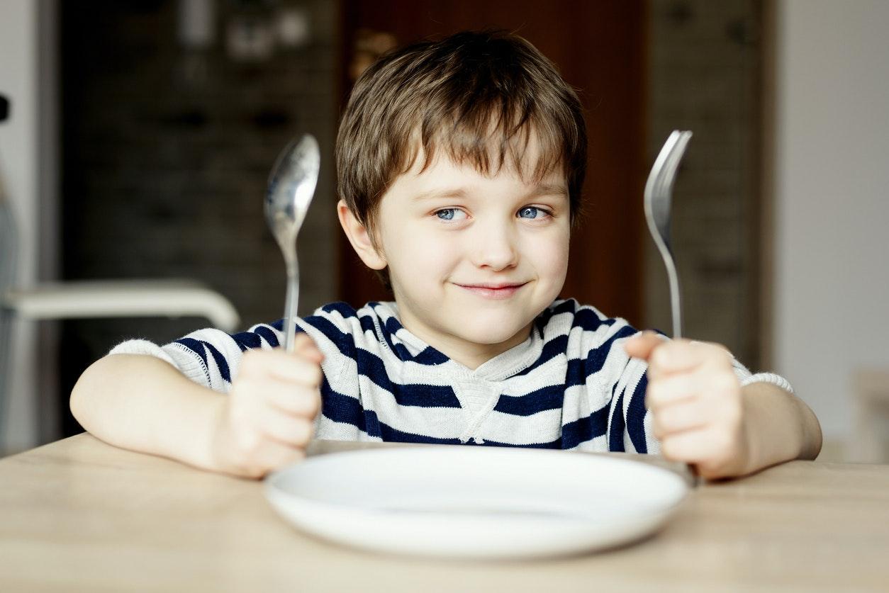 Enfant Heureux à Table Qui Attend Son Repas