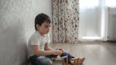 enfant assis par terre dans sa chambre