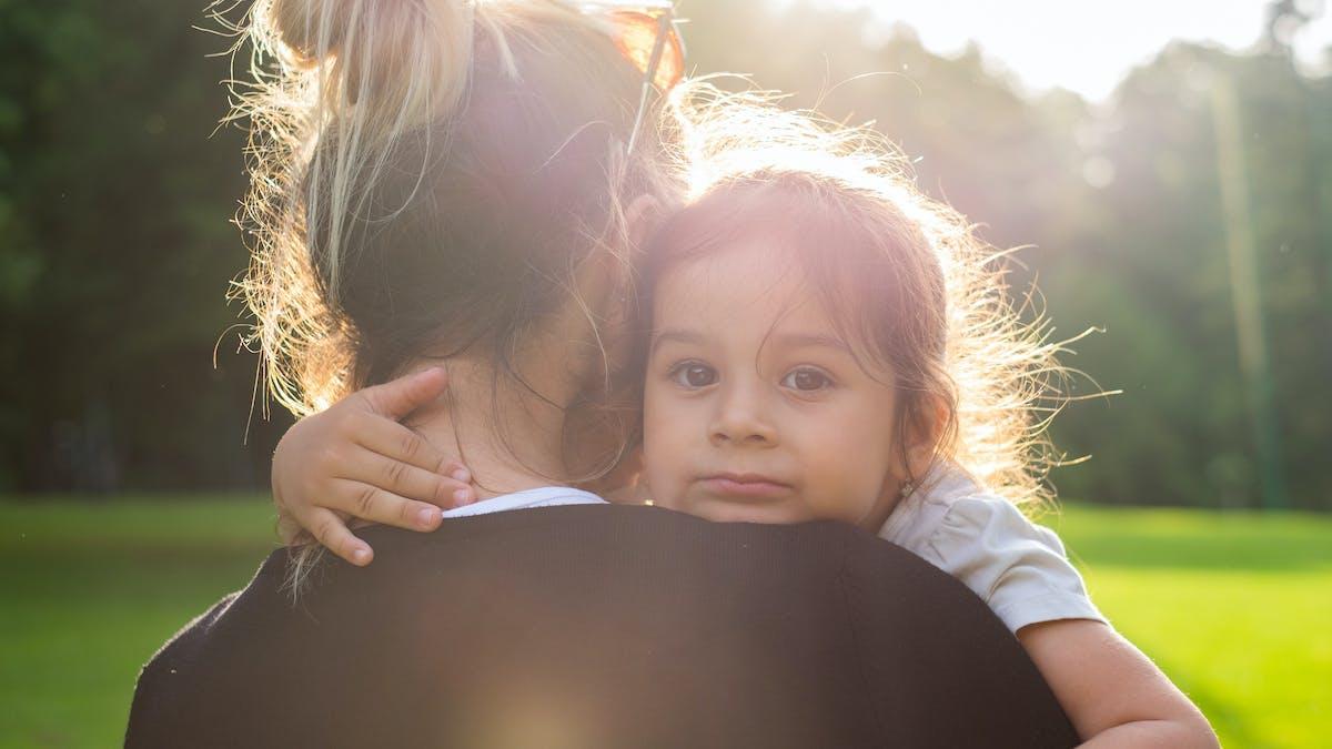 petite fille dans les bras de sa mère