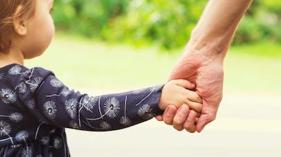 gros plan d'un bébé qui marche en tenant la main de sa grand-mère