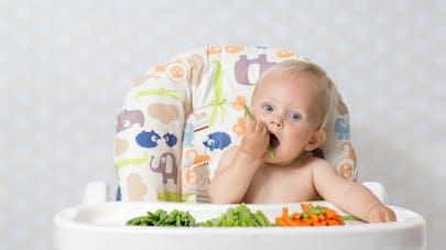 bébé qui mange à la main des légumes crus