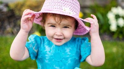 Petite fille qui tient son chapeau