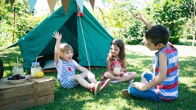 enfants jouent devant une tente