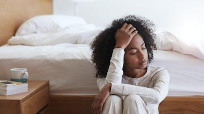 femme début de grossesse assise au pied du lit incapable de se lever