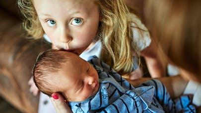 grande soeur qui embrasse son petit frère nouveau-né