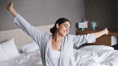 Femme s'étirant dans son lit