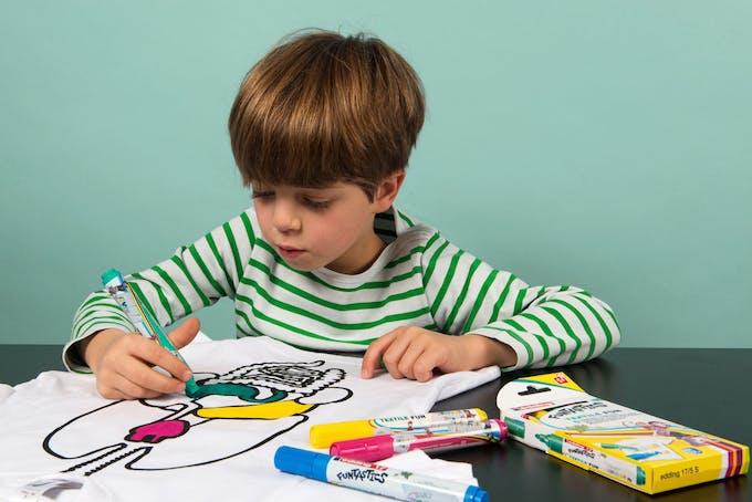 enfant qui colorie le tee-shirt avec organes koa koa