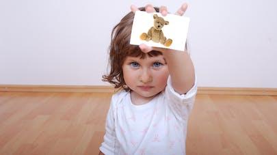 petite fille qui montre une carte objet dans le cadre de l'apprentissage PECS