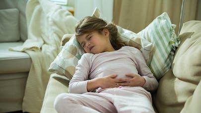enfant qui a mal au ventre sur le canapé