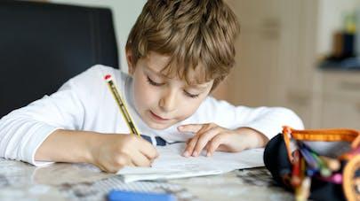 enfant très concentré sur son écriture