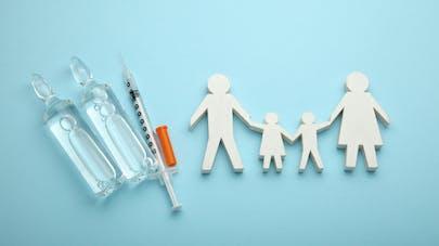 nature morte une seringue de vaccin et une famille en papier