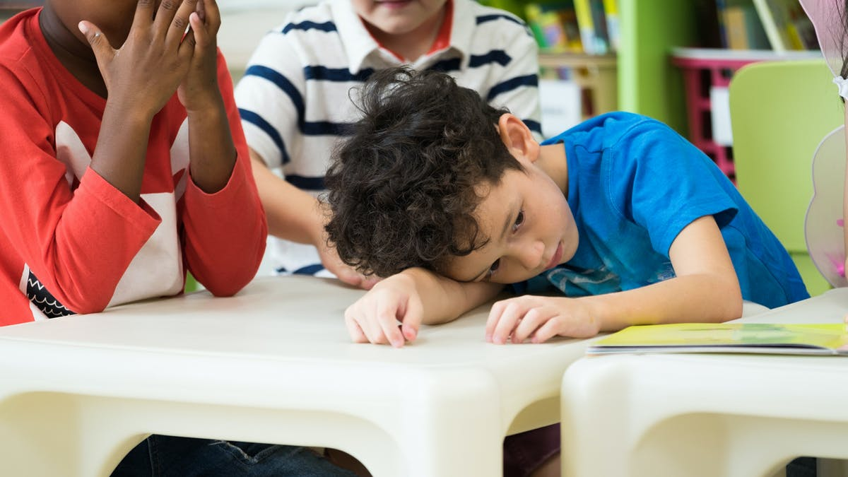 enfant gêné en classe de maternelle