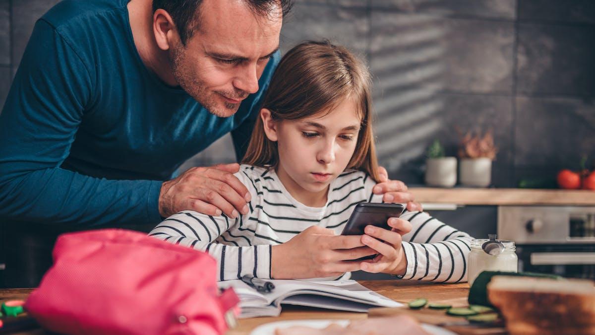 un papa et sa fille de 10 ans avec un téléphone portable.