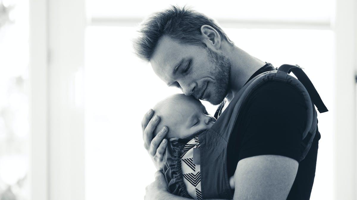 jeune père avec son bébé dans un porte bébé