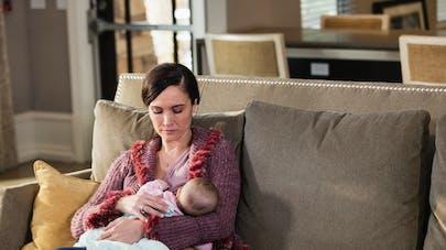 mère sur le canapé avec son bébé en l'allaitant