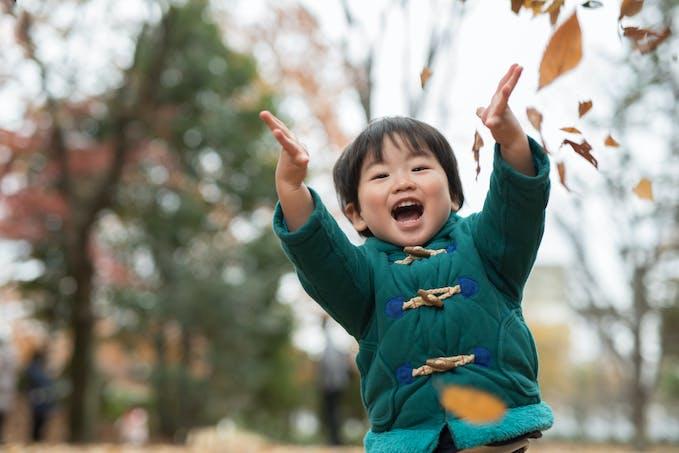 Enfant qui jette des feuilles
