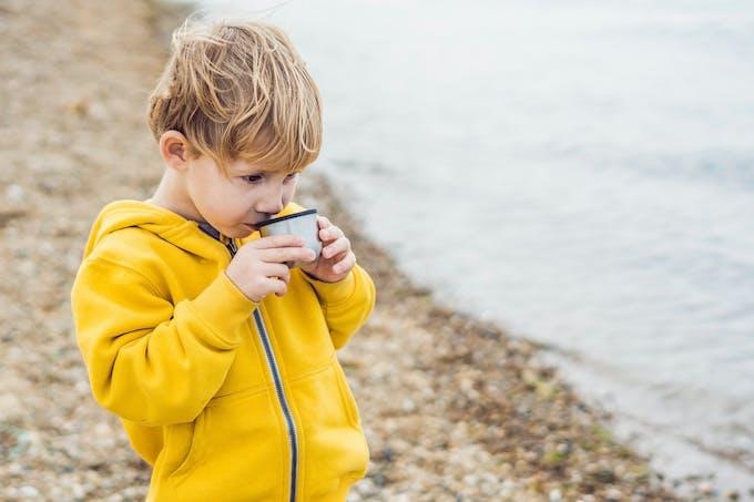 Petit garçon qui boit une tasse portant ciré jaune
