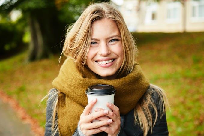 Femme qui tient un café