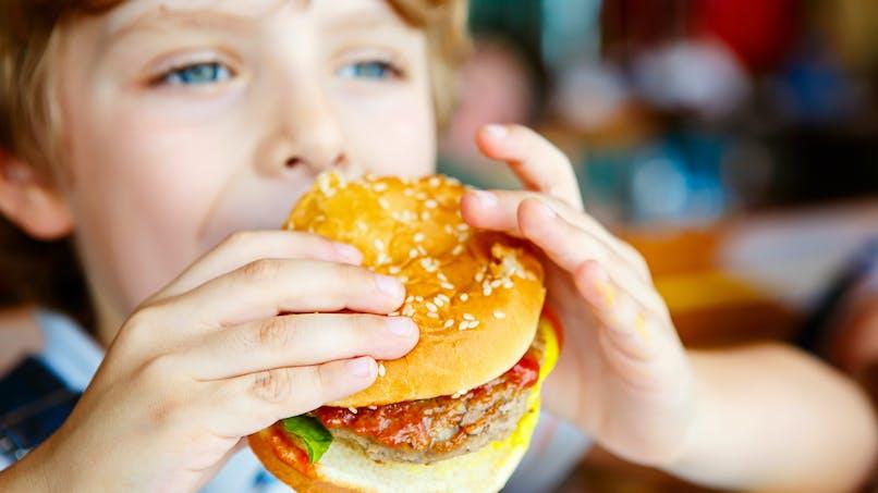 Alimentation: un enfant mange un hamburger et se coupe la lèvre