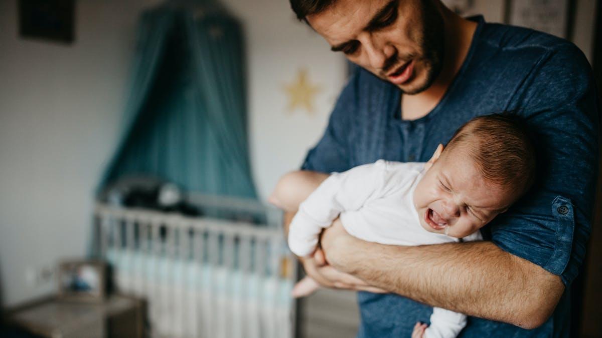 bébé qui pleure dans les bras de son père