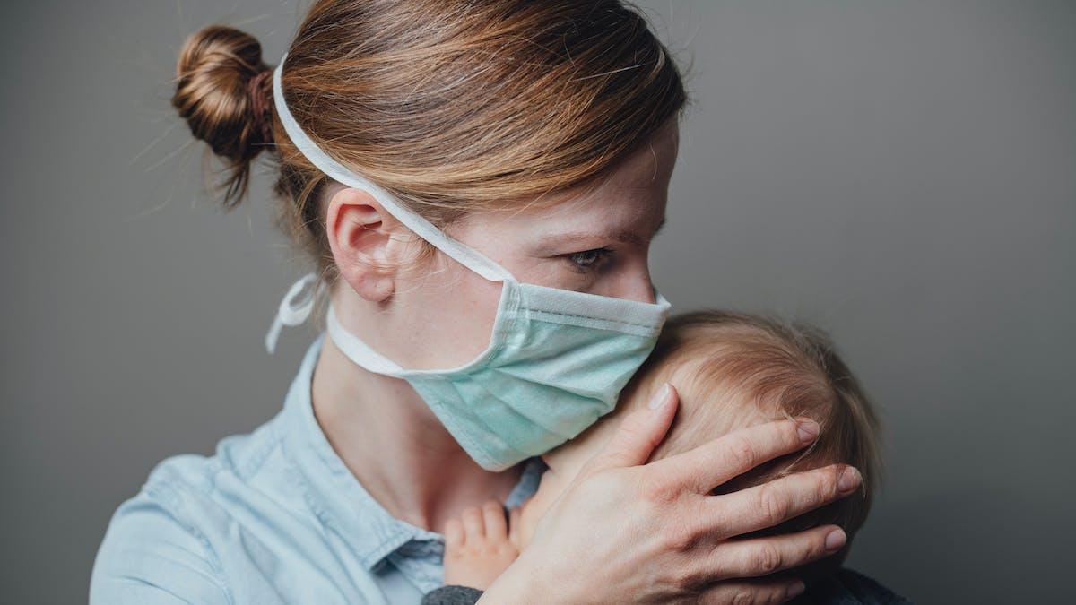 femme masquée avec un bébé