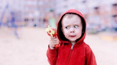 enfant daltonien regarde un jouet rouge