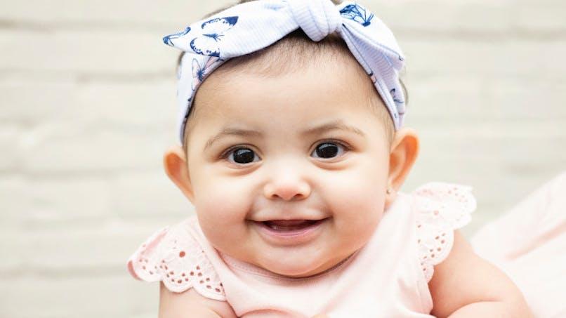 bébé souriant avec noeud dans cheveux