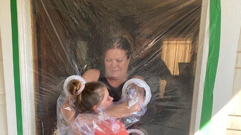 Le rideau à câlins : cette fillette a trouvé le moyen d'enlacer ses grands-parents tout en respectant les gestes barrières