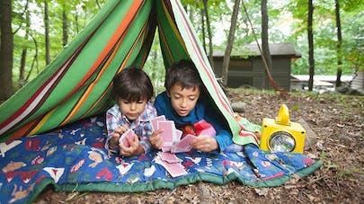deux garçons jouent aux cartes sous une tente