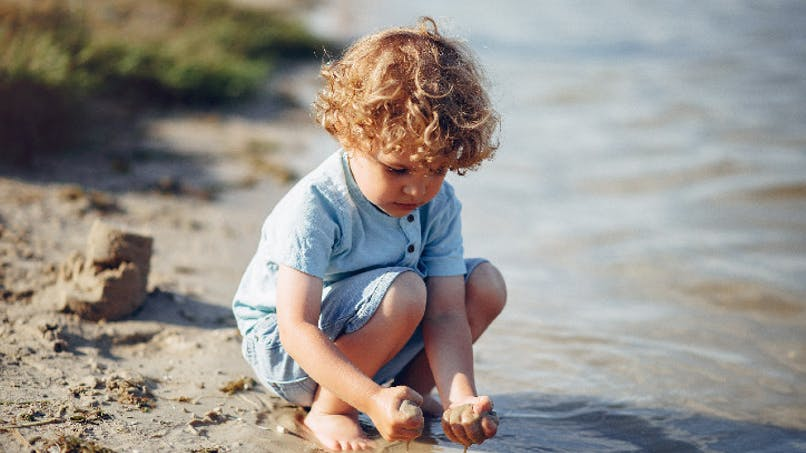 garçon jouant avec le sable