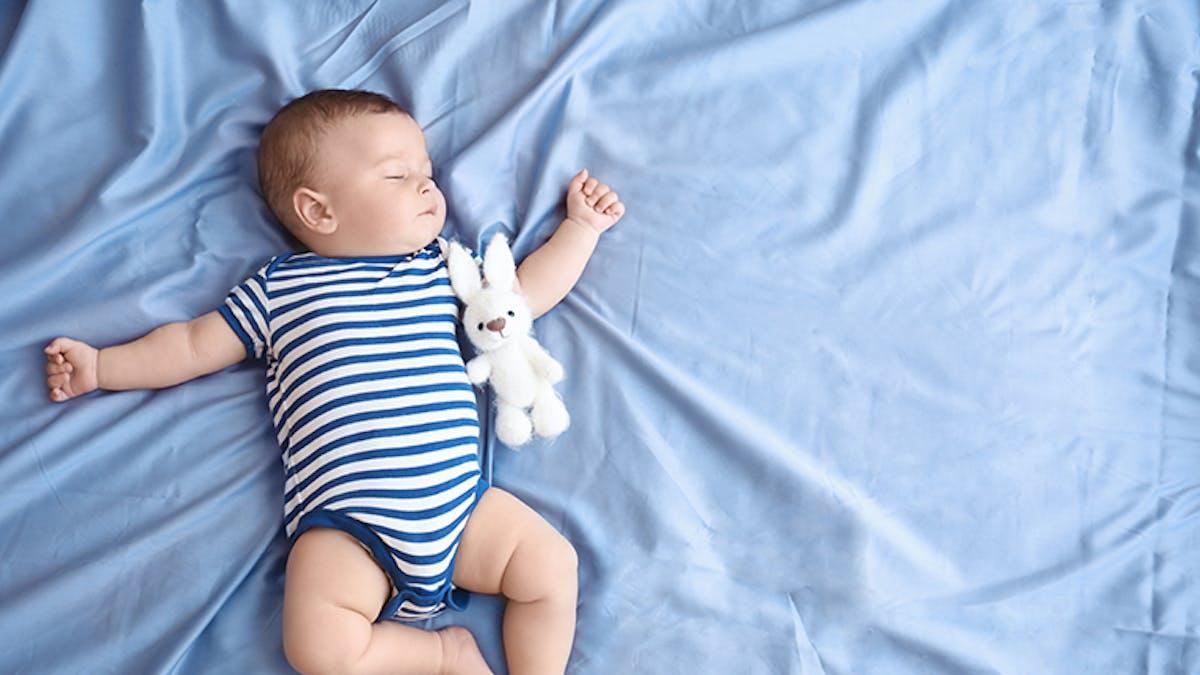bébé dort sur le dos avec son doudou