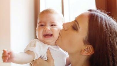 Bébé pleure dans les bras de sa maman