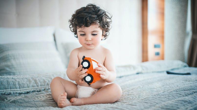 >Bébé qui tient une voiture