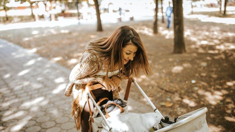 Maman penchée au-dessus du landau de bébé dans un parc