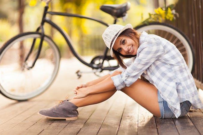 Femme assise à côté d'un vélo
