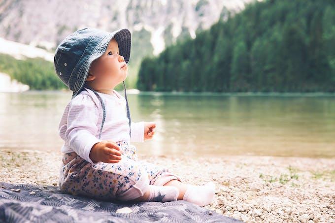 bébé au bord de l'eau avec un bob sur la tête